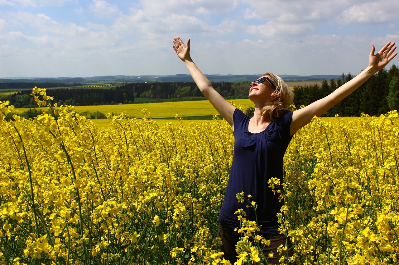 Woman expressing gratitude in field of flowers