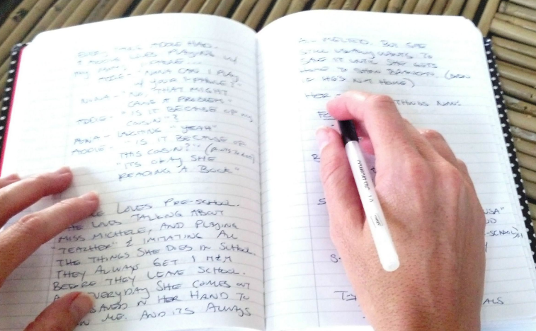 A hand holds a pen over a full page of lined writing paper in a notebook.